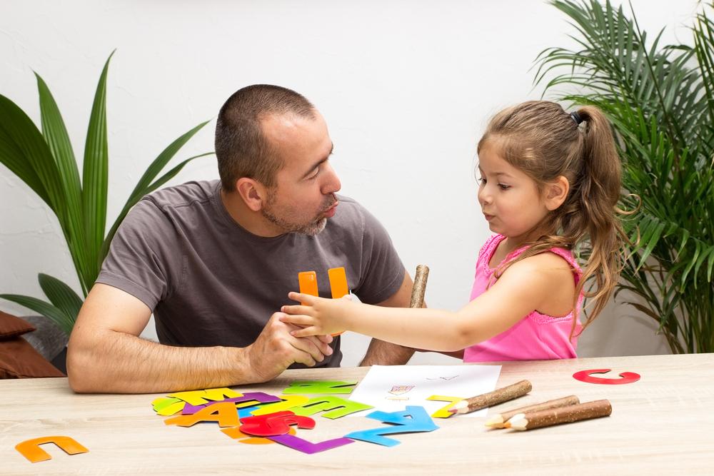 מטפל וילדה מתרגלים טיפול בגישה התנהגותית מחזיקים אותיות מנייר